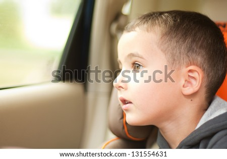 Curious little boy in the car watching the window sitting in safe chair #131554631