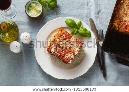 vegan lasagna with lentils and green peas in a baking sheet on a table with a blue linen tablecloth. healthy Italian cuisine for the whole family, party or restaurant and red wine in glasses #1315588193