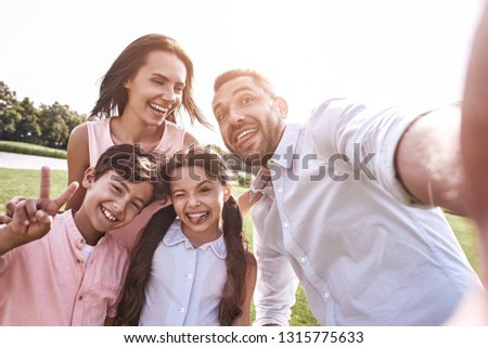 Beautiful memories. Family of four taking selfie photo on smartp