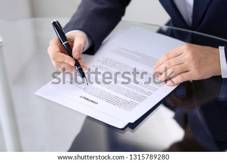 Unknown female hands with pen over document of contract. Agreement signing or business concept #1315789280