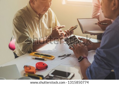 Close up hand of civil engineer or architect business useing calculator about calculate the cost with  for working building plan design project in office.  #1315850774