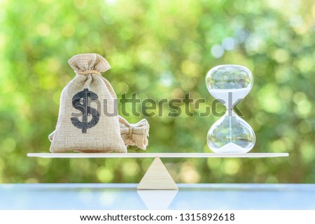 Time value of money, asset growth over time, financial concept : Dollar bags, sand clock or hourglass on a balance scale in equal position, depicts investment in long-term equity for more money growth #1315892618