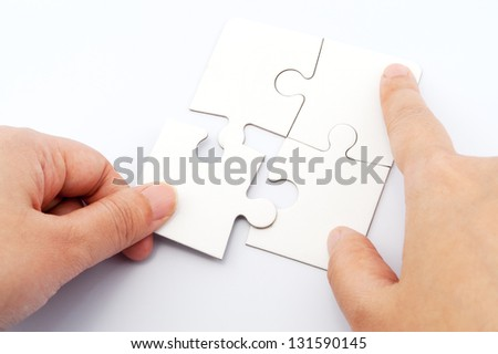 Hand holding puzzle piece and inserting it into group of white paper jigsaw puzzles #131590145