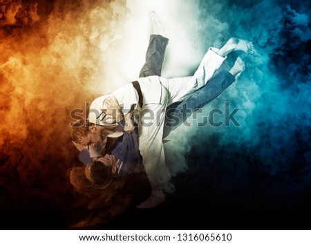 The two judokas fighters fighting man on smoke background #1316065610