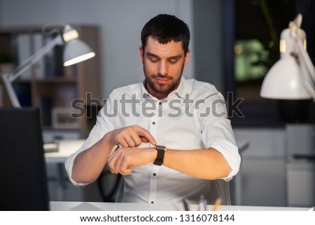 business, technology and time management concept - happy smiling businessman with smart watch at nigh office #1316078144