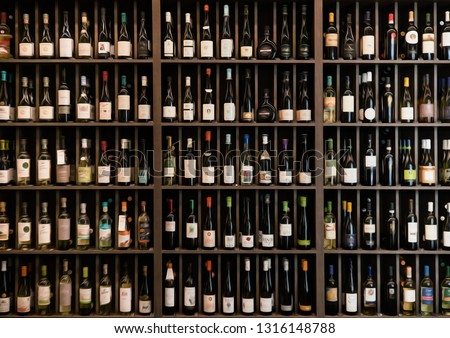 Collection of wines in the store of elite alcohol. Bottles of various wines are beautifully on the rack. Paint effect. #1316148788