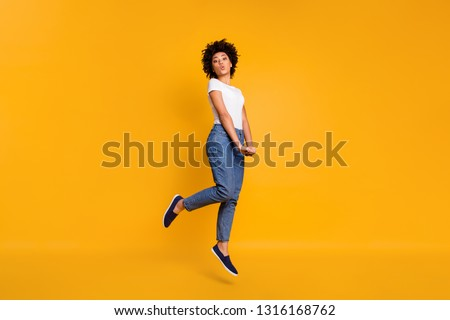 Full length body size side profile photo jumping high beautiful she her lady sending kisses graceful hands arms together wearing casual jeans denim white t-shirt clothes isolated yellow background #1316168762
