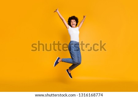 Full length body size side profile photo jumping high beautiful she her lady hands arms up win game play match wearing casual jeans denim white t-shirt clothes isolated yellow bright vivid background #1316168774