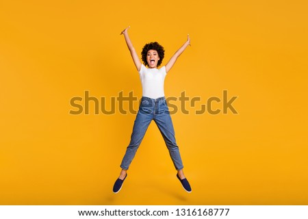 Full length body size photo jumping high beautiful she her lady hands arms separate in star shape figure win wearing casual jeans denim white t-shirt clothes isolated yellow bright vivid background