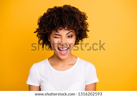 Close up photo pretty amazing she her dark skin lady cool look glad winking one eye mouth open laugh laughter wearing casual white t-shirt isolated yellow bright vibrant vivid background #1316202593