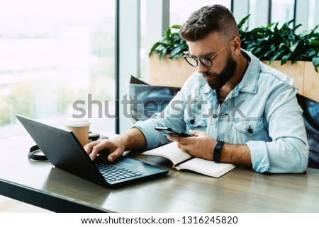 Hipster man sits in cafe, uses smartphone, works on laptop. Businessman reads an information message in phone. Freelancer works outside office. Teleworking. Online marketing, education for adult. #1316245820