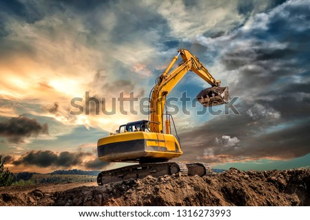 Crawler excavator during earthmoving works on construction site at sunset Royalty-Free Stock Photo #1316273993