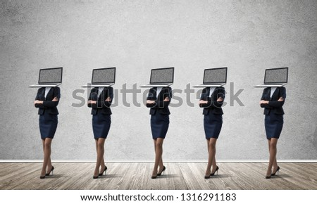 Business women in suits with laptops instead of their heads keeping arms crossed while standing in a row in empty room with gray wall on background. #1316291183