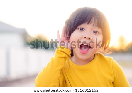 Little asian girl holds her hand near her ear and listening something.Exciting face on funny child girl wear yellow shirt in winter time and listening to curious good news.  #1316312162