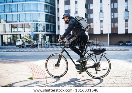 Male courier with bicycle delivering packages in city. Copy space. #1316331548
