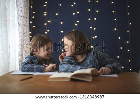 Girlfriends sisters do fun lessons together and show each other tongue a real interior and a blue wall, concept homework and home schooling #1316348987