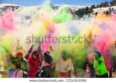 """Seli, Greece - February 17, 2019: Crowds of unidentified people throw colour powderduring the annual winter event """"Day of Colours"""" in the snowy landscape #1316361086"""