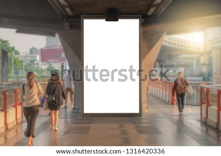 large blank advertise billboard white LED screen vertical on big concrete pole walk way outdoor in city with people walking go to working on morning.