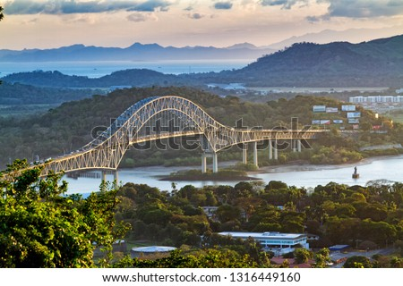 Panoramic aerial view of the Bridge of The Americas over the Panama Canal Pacific Entrance. Sunset scene with a gentle mist in the background. The bridge is spanning two continents - two Americas. #1316449160