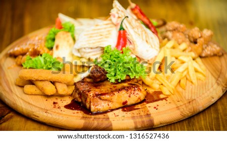 Snack for beer. Wooden board french fries fish sticks burrito and meat steak served with salad. Pub menu snack. Enjoy your meal. Meat snack for group friends. Tasty delicious snacks. Restaurant food. #1316527436