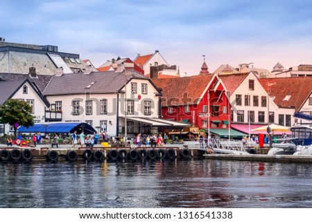 Stavanger, Norway - August 2, 2018: City street view with people, cafe, restaurants and colorful traditional wooden houses at promenade near harbour #1316541338
