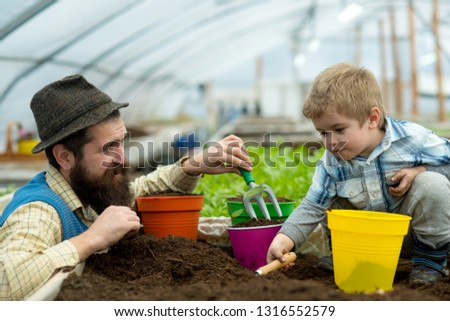 father and child. father and child work in greenhouse. happy family of father and child. father and child at fathers day work in garden. keeping plants hydrated #1316552579