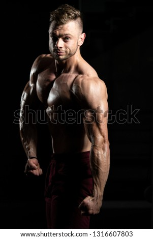 Young Man Standing Strong In The Gym And Flexing Muscles - Muscular Athletic Bodybuilder Fitness Model Posing After Exercises #1316607803