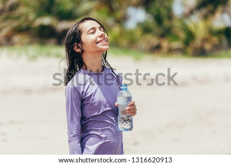 Portrait of little girl drinking water on the beach #1316620913