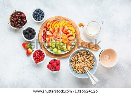 Grain free paleo style granola or vegan muesli made from nuts. Fruit berries platter, strawberries blueberries raspberries peach figs red currant, overhead view, selective focus #1316624126