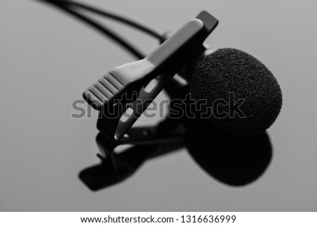 Lapel microphone with a tie-clip on a dark glossy surface.