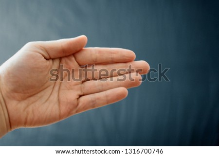 Adult hand with Raynaud's Syndrome - Phenomenon. Close up hand with fingers on dark background with copy space #1316700746