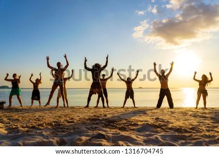 KOH PHANGAN, THAILAND - FEBRUARY 18, 2019 : Young peope dancing at tropical beach near sea water at paradise island at sunset. Summer concept. Holiday travel. #1316704745