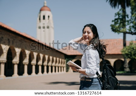 asian college girl standing outdoor going to class at school in summer tour program. elegant smart exchange student study overseas in stanford usa. young woman freshman in new semester cheerful smile #1316727614
