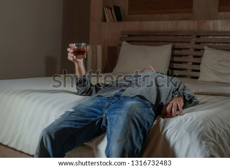 young messy and wasted drunk man drinking whiskey glass at home lying on bed hammered and dizzy as alcoholic suffering alcoholism problem and alcohol addiction intoxicated and lost #1316732483