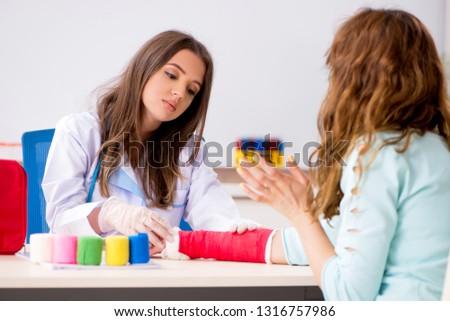Female doctor traumatologist bandaging female patient   #1316757986