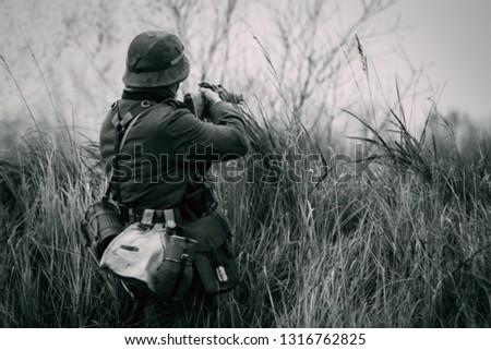 A soldier of the German army Wehrmacht during the Second World War shoots at the enemy from behind the shelter in full growth. Black and white photo #1316762825