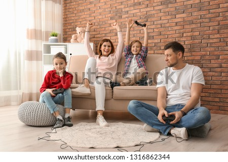 Happy family playing video games in living room #1316862344