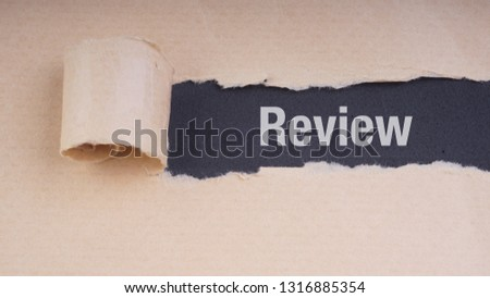 REVIEW text on brown envelope and torn paper. Concept Image #1316885354