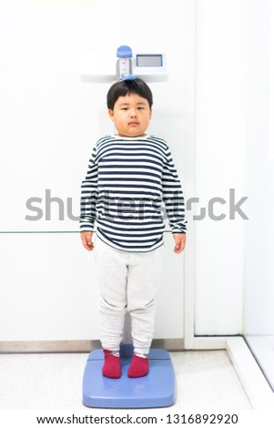 A fat boy is measuring his height and his weight himself in hospital #1316892920