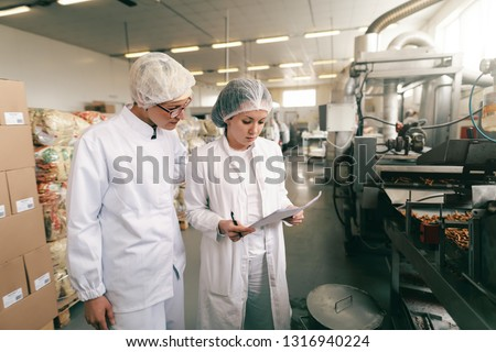 Two quality professionals in white sterile uniforms checking quality of salt sticks while standing in food factory. #1316940224