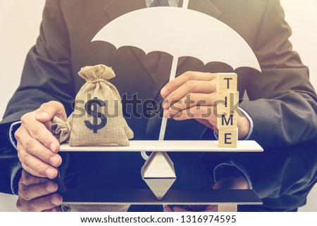 Time value of money, asset growth over time concept : Businessman protects or shields US dollar bags on a basic balance scale, depicts rising of present value when depositing or saving money in a bank #1316974595