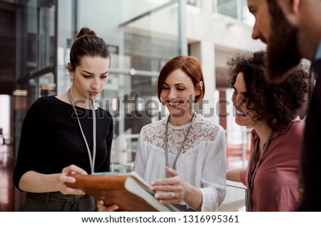 Group of young businesspeople standing together in office, talking. #1316995361
