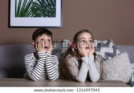 Cute little children watching cartoons on TV late in evening