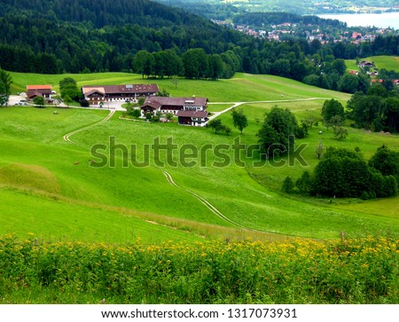 Panoramic view over fields houses and lake with hills in the background,  #1317073931