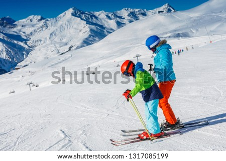 Cute happy skier boy with his mother having fun in a winter ski resort. #1317085199