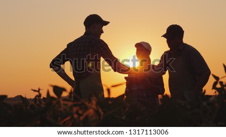A group of farmers in the field, shaking hands. Family Agribusiness #1317113006