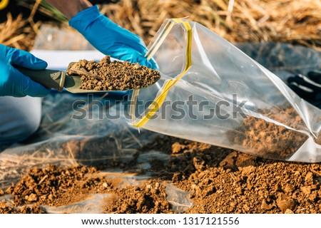 Soil Test. Agronomist putting soil with garden shovel in soil sample bag outdoor. Environmental research #1317121556