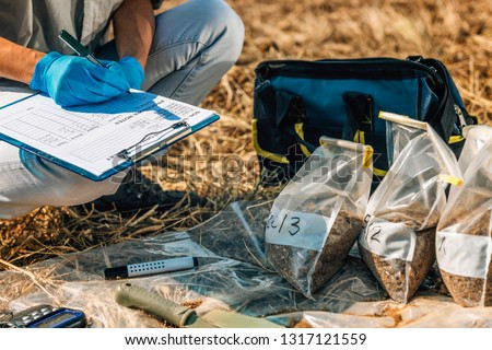 Soil Test. Female agronomist taking notes in the field. Environmental protection, organic soil certification, research Royalty-Free Stock Photo #1317121559