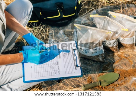 Soil Test. Female agronomist taking notes in the field. Environmental protection, organic soil certification, research Royalty-Free Stock Photo #1317121583