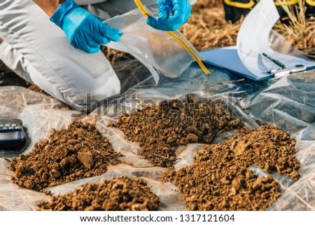 Testing Soil. Agronomist opening soil sample bag in the field. Environmental protection, organic soil certification, Soil Fertility Analysis #1317121604